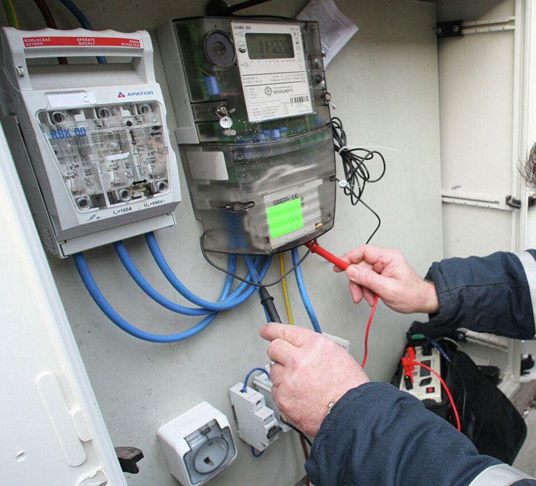 Электрик проверяет напряжение в щитке